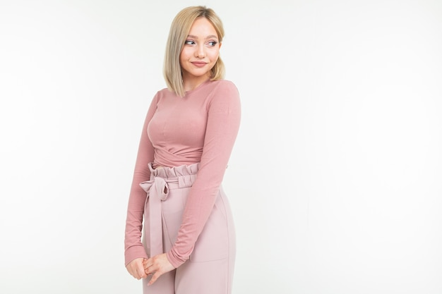 Young attractive woman in pink clothes posing on white background with copy space