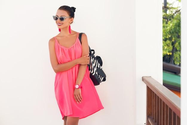 Giovane donna attraente in abito rosa contro il muro, tenendo lo zaino, indossando occhiali da sole hipster, accessori moda, street style moderno, tendenza estiva, viaggiando in vacanza, sorridente, emozione felice