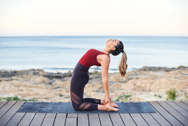 Young attractive woman practices yoga in camel pose on the beach.