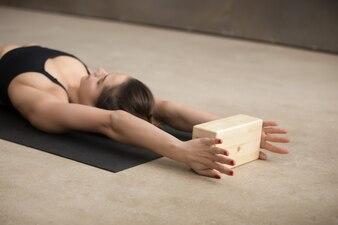 Молодая привлекательная женщина практикующих йогу Айенгара с помощью деревянного блока