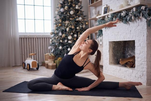 現代の家でヨガを練習している若い魅力的な女性