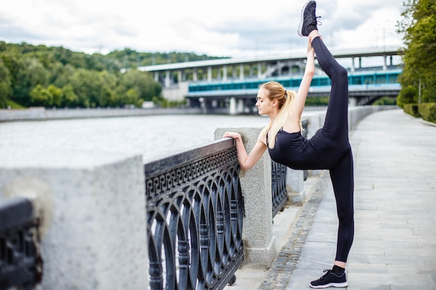 Young attractive woman practicing yoga, city and river background.