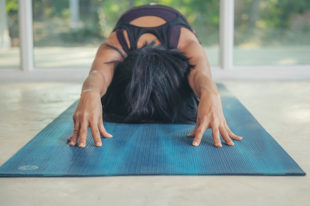 Young attractive woman practicing yoga exercise at home, working out, wearing sportswear, pants and top, indoor full length, balasana, child pose, ardha-kurmasana.