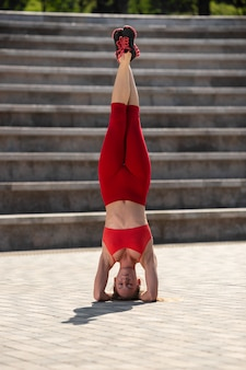 Young attractive woman practicing yoga outdoors. the girl performs a handstand upside down