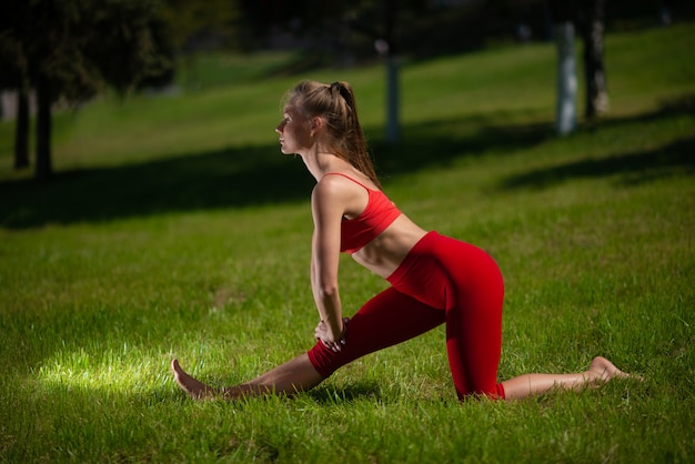Young attractive woman practicing yoga outdoors. the girl performs various exercises on the grass