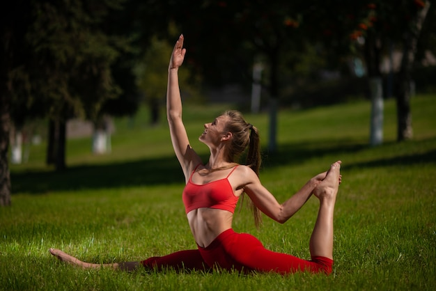 Young attractive woman practicing yoga outdoors, the girl performs various exercises on the grass