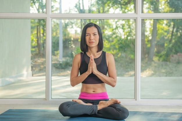 Giovane donna attraente che pratica yoga, seduta a padmasana, esercizio fisico, posa del loto, namaste, allenamento, abbigliamento sportivo, pantaloni neri, lunghezza interna, vicino alla finestra del pavimento.