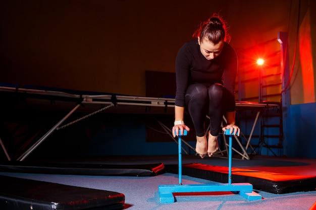 ヨガを練習している若い魅力的な女性、手でバランスをとる運動、逆立ち、トレーニング、スポーツウェア、黒いレギンスとトップ、屋内で完全に成長している