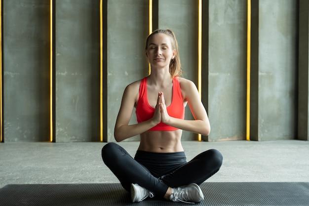 Молодая привлекательная женщина, практикующая йогу, женщина, практикующая йогу и медитацию в позе лотоса