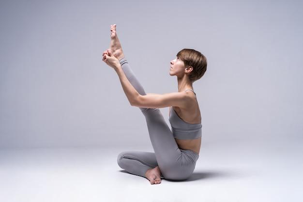 Молодая привлекательная женщина практикует йогу, работает, носить спортивную одежду