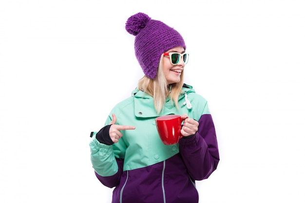 Young attractive woman in purple ski suit hold red cup