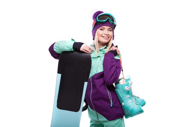 Young attractive woman in purple ski suit hold snow boots and snowboard