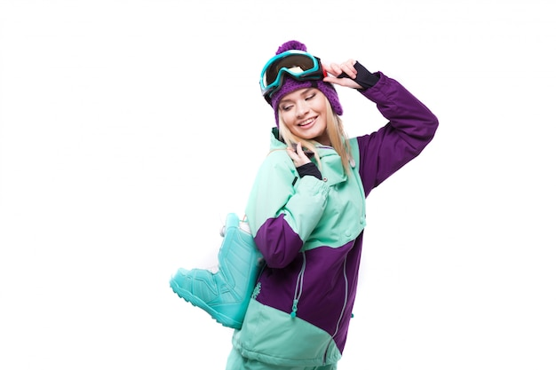 Young attractive woman in purple ski suit hold snow boots
