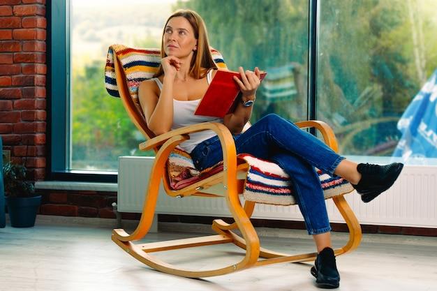 Молодая привлекательная женщина читает книгу, качаясь в удобном кресле-качалке. хорошо проведенное время поднимет вам настроение.