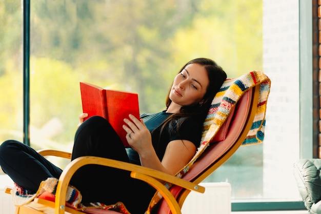 若い魅力的な女性は、快適なロッキングチェアで揺れながら、本を読みます。楽しい娯楽はあなたの気分を改善します。