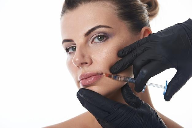 Молодая привлекательная женщина получает инъекцию в губы косметологом в черных защитных медицинских перчатках