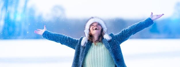 젊은 매력적인 여자는 겨울에 떨어지는 눈에 기뻐합니다. 배너.