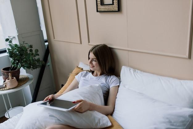 Молодая привлекательная женщина, расслабляющаяся на белом диване у окна дома