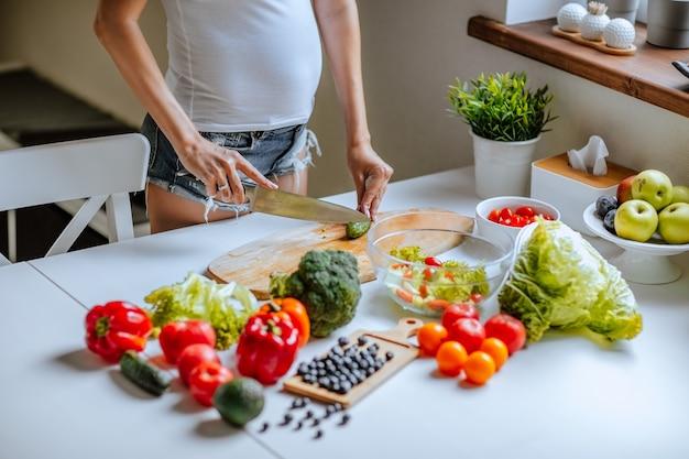 Беременное тело молодой привлекательной женщины в белой рубашке и джинсовых шортах позирует возле белой кухни