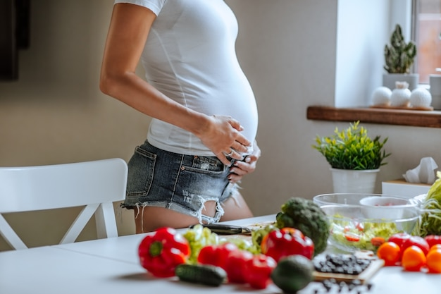 Беременное тело молодой привлекательной женщины в белой рубашке и джинсовых шортах позирует
