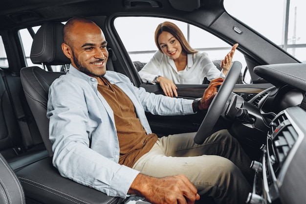 Young attractive woman salesperson in car showroom showing a car to her male client