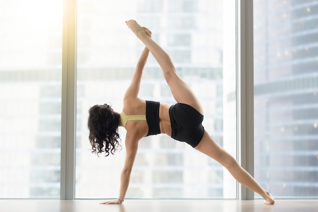 Young attractive woman in side plank pose against floor window