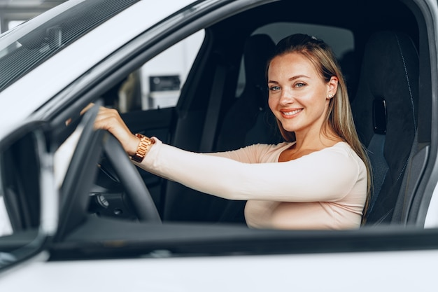 Young attractive woman sits in her newly bought car in dealership