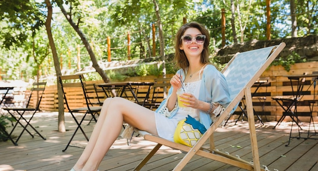 Young attractive woman sitting in deck chair in summer fashion outfit, hipster style, white dress, blue cape, sunglasses, drinking lemonade, stylish accessories, relaxing, long skinny legs in sandals