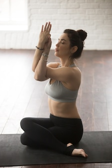 Young attractive woman sitting in gomukasana, white loft studio