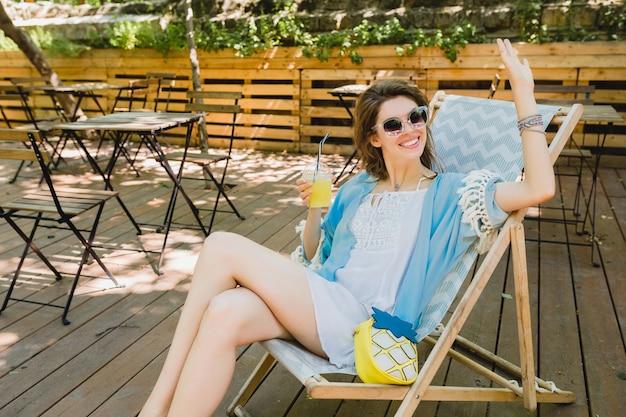 夏のファッションの衣装、白いドレス、青いケープ、サングラス、笑顔、レモネード、スタイリッシュなアクセサリーを飲んで、休暇でリラックスのデッキチェアに座っている若い魅力的な女性