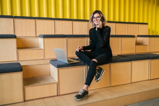 Молодая привлекательная женщина, сидящая в лекционном зале, работающая на ноутбуке, в очках, современная аудитория, студенческое образование онлайн, фрилансер, улыбается, разговаривает по телефону