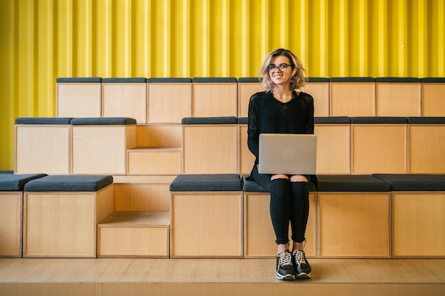 Молодая привлекательная женщина, сидящая в лекционном зале, работающая на ноутбуке, в очках, современная аудитория, студенческое образование онлайн, фрилансер, улыбается, подростковый стартап, смотрит в камеру, счастливый
