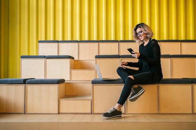 Молодая привлекательная женщина, сидя в лекционном зале, работает на ноутбуке, в очках, современная аудитория, студенческое образование онлайн, фрилансер, улыбаясь, с помощью смартфона, цифровых устройств