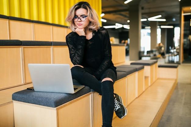 Молодая привлекательная женщина, сидя в лекционном зале, работает на ноутбуке в очках, современная аудитория, обучение студентов в интернете, беспокоятся, думая о проблеме