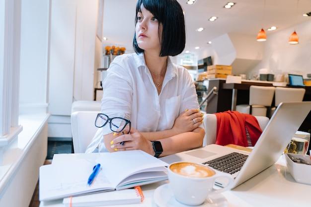 オフィスでコワーキングに座って、ラップトップのキーボードコンピューターで入力し、朝にメモをとる若い魅力的な女性。電話、ノート、グラス、コーヒー1杯を備えたデスク。ビジネスコンセプト