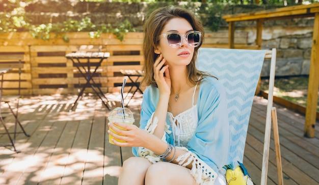 夏のファッションの衣装、流行に敏感なスタイル、白いドレス、青いケープ、サングラス、レモネード、スタイリッシュなアクセサリーを飲んで、日当たりの良い休暇でリラックスできるデッキチェアで日陰に座っている若い魅力的な女性