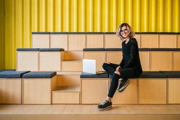 Young attractive woman sitting in lecture hall, working on laptop, wearing glasses, modern auditorium, student education online, freelancer, smiling, teenage startup