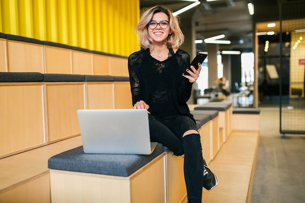 Young attractive woman sitting in lecture hall, working on laptop, wearing glasses, modern auditorium, student education online, freelancer, smiling, using smartphone, looking in camera