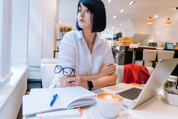 Young attractive woman sitting in office coworking and typing on her laptop keyboard computer and making notes in morning. desk with a phone, notebook, glasses and a cup of coffee. business concept