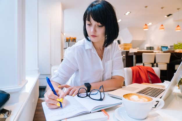 Young attractive woman sitting in office, writing on notebook