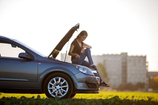 Молодая привлекательная женщина, сидящая на машине с выскочившим капотом, проверяющая уровень масла в двигателе с помощью щупа на фоне копией пространства ясного неба. транспорт, проблемы с транспортными средствами и концепция поломок.