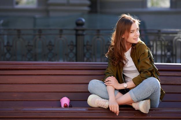 公共の公園のベンチに座っている若い魅力的な女性は一杯のコーヒーを飲み、夏を楽しむ