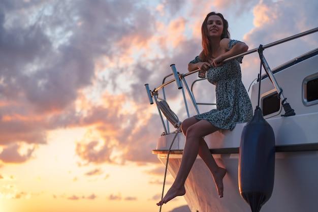 요트 갑판에 앉아 일몰을 즐기는 젊은 매력적인 여성