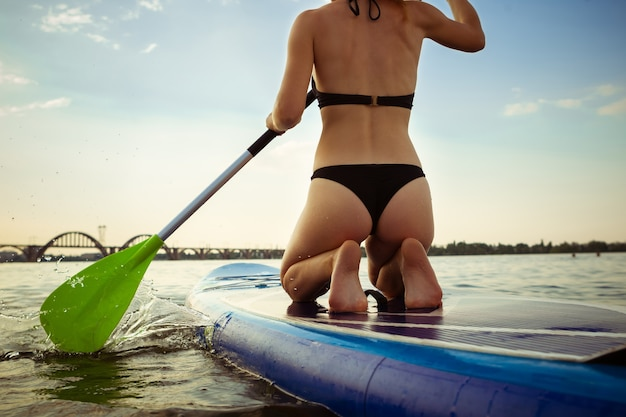 Young attractive woman sitting on paddle board, sup. active life, sport, leisure activity concept