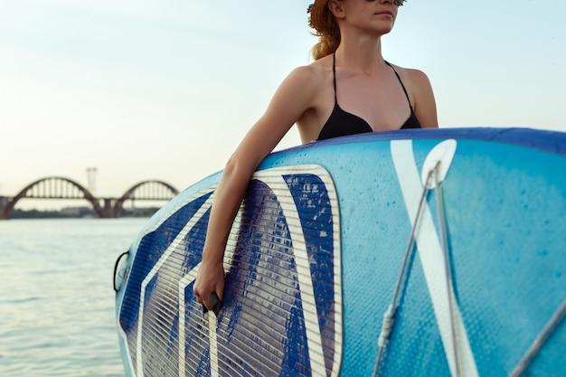 Giovane donna attraente che si siede sul paddle board