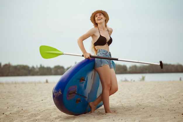 Young attractive woman sitting on paddle board