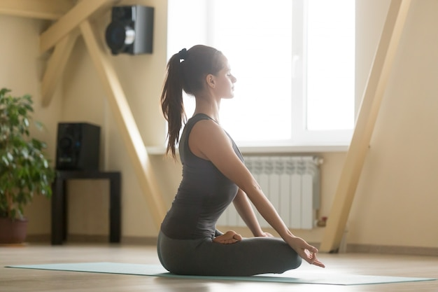 Young attractive woman sitting in padmasana pose, home interior,