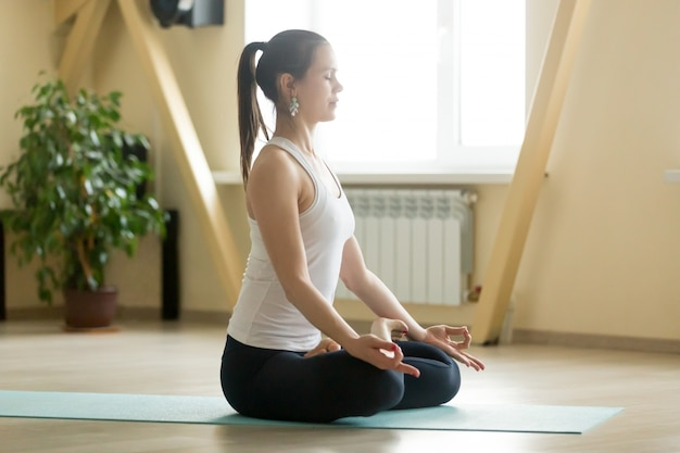 Young attractive woman sitting in padmasana pose, home interior