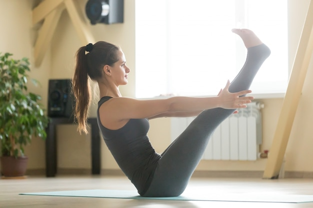 Young attractive woman sitting in paripurna navasana pose, home