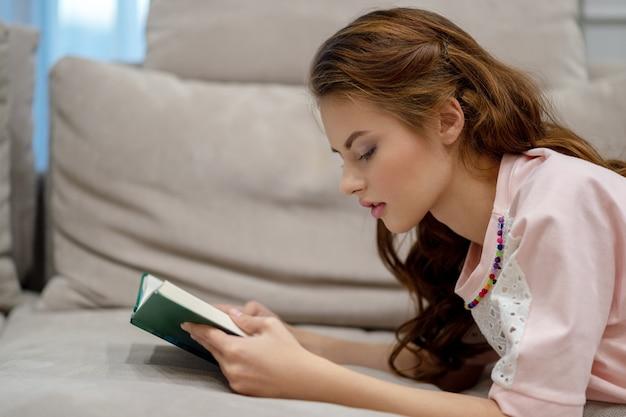 Giovane donna attraente che si siede sul sofà che legge un libro